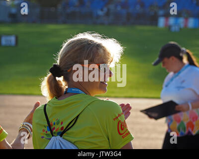Sheffield, UK. 10th August, 2017. A volunteer and an official enjoy the sunshine at the Special Olympics National Games in Sheffield after a downpour dampened spirits at the opening ceremony Credit: Steve Holroyd/Alamy Live News - Stock Image