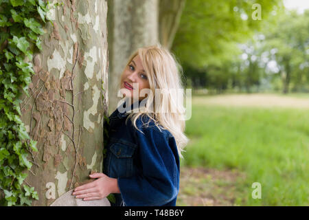 Beautiful young blonde woman hugging a huge old tree - Stock Image