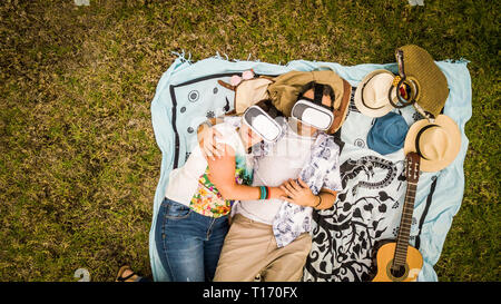 Alternative couple in relationship lay down i love with guitar and goggled headset - technology adults nerd addicted in outdoor leisure activity toget - Stock Image
