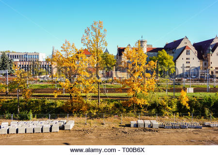 Poznan, Poland - October 31, 2018: Trees and construction area with university building in the background. - Stock Image