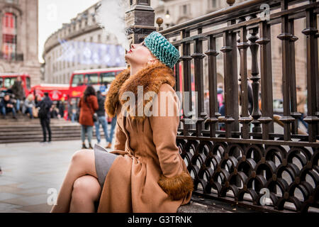 A stylish young woman dressed in 1930s style clothing sitting smoking by railings at the entrance to Piccadilly - Stock Image