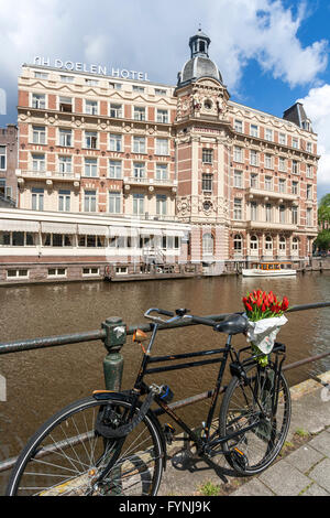 NH Doelen Hotel, bicycle with tulips, Amsterdam, Netherlands - Stock Image