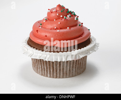 A single decorated red cupcake on a white background. - Stock Image