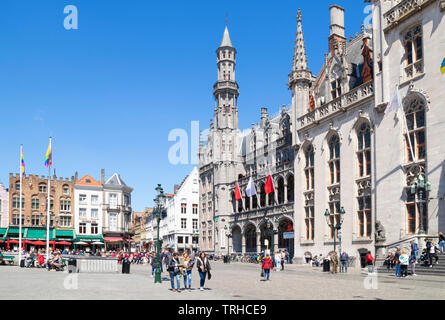 Tourists wandering around the historic market place going past the Provincial Court Provinciaal Hof in the Markt central Bruges Belgium EU Europe - Stock Image
