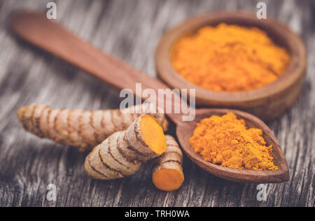 Raw turmeric with powder in a bow and spoonl on wooden surface - Stock Image