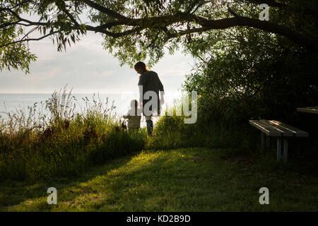 Mother with son (18-23 months) standing by sea - Stock Image