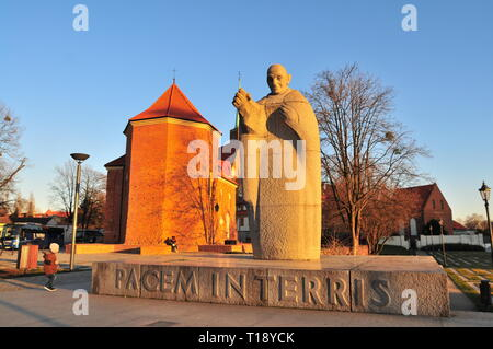 Pope John XXIII Granite Statue with Roman Catholic church of St. Marcin in the back. Wroclaw Ostrow Tumski. Poland - Stock Image