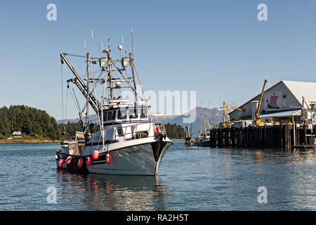 A fishing boat enters the docks in the tiny village of Petersburg on Mitkof Island along the Wrangell Narrows in Frederick Sound with the Alaska Coast Range of mountains behind on Mitkof Island, Alaska. Petersburg settled by Norwegian immigrant Peter Buschmann is known as Little Norway due to the high percentage of people of Scandinavian origin. - Stock Image