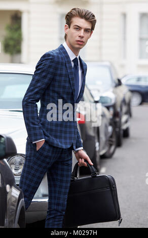 Young man in blue checked suit about to cross the street - Stock Image
