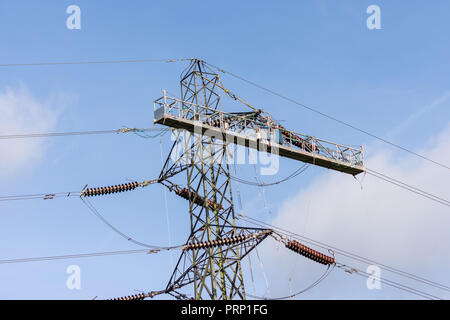A temporary work platform attached to an electricity pylon for workers to carry out power line replacement - Stock Image