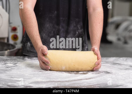 Baker kneading fresh raw bread dough at the bakery . - Stock Image