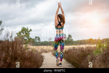 woman doing exercises in the morning sun, back view. - Stock Image