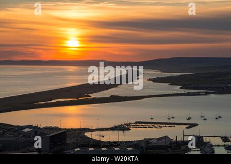 Portland, Dorset, UK.  4th July 2019. UK Weather.  A spectacular fiery sunset over the Fleet lagoon and Chesil beach on the Dorset Jurassic Coast viewed from the Isle of Portland.  Picture Credit: Graham Hunt/Alamy Live News - Stock Image