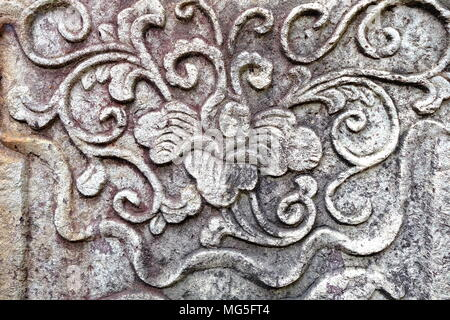 Vintage Thai Sculpture on Stone Wall. - Stock Image
