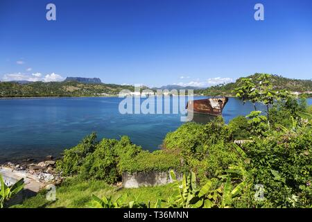 Landscape View of Baracoa Bay Harbour with Old Rusted Ship and Distant El Yunque Landmark Tabletop Mountain on East Coast of Cuba - Stock Image