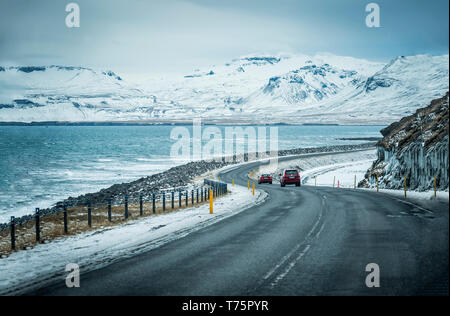 Modern car riding on asphalt countryside road towards magnificent snowy mountains during trip through Iceland - Stock Image