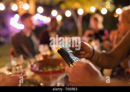 Woman paying for dinner with smart card on patio - Stock Image