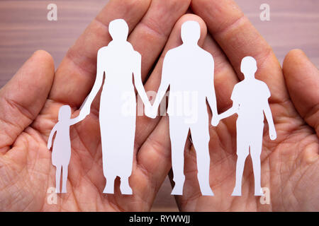 Family Cutout Paper With The Protection Of Cupped Hands Over Wooden Desk - Stock Image