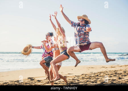 Happiness and joy for young people on vacation at the beach - enjoy outdoor leisure activity for group of friends in summer holiday - jump and laugh a - Stock Image