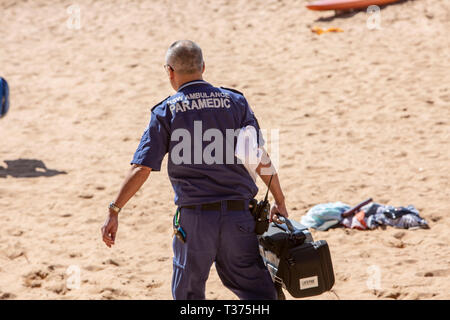 Male paramedic from NSW Ambulance walks across the sand at Palm beach to assist a near drowning victim who was saved by surf rescue volunteers,Sydney, - Stock Image
