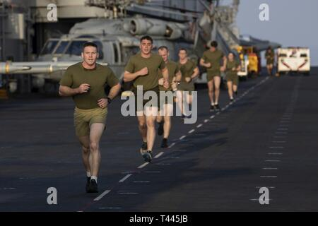 GULF OF OMAN (March 17, 2019) – U.S. Marines with the 22nd Marine Expeditionary Unit run on the flight deck during a physical fitness test aboard the Wasp-class amphibious assault ship USS Kearsarge (LHD-3). Marines performed the test before starting a Martial Arts Instructor Course to ensure they could meet the physical demands of the training. Marines and Sailors with the 22nd MEU and Kearsarge Amphibious Ready Group are currently deployed to the U.S. 5th Fleet area of operations in support of naval operations to ensure maritime stability and security in the Central region, connecting the Me - Stock Image