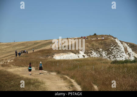 Beachy Head, UK - July 14 2018: Tourists walk on the hilltop of the chalk sea cliff at Beachy head on a hot summers day on 14 July 2018. Temperatures raised to 27 degrees and is expected to stay high for another month. The cliff, the highest chalk sea cliff in Britain rises to 162 metres above sea level and unfortunately one of the most notorious suicide spots in the world. Credit: David Mbiyu - Stock Image