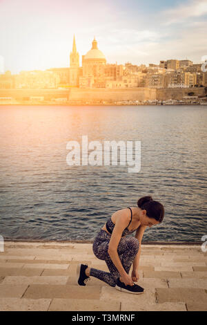 woman doing up her running shoes with Valletta city background with sun lens flare - Stock Image