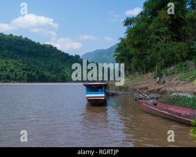 Tourist boat moored at the side of the mighty Mekong River at entrance to Ban Xiang Hai the Whiskey village Laos Asia famous for locally produced rice - Stock Image
