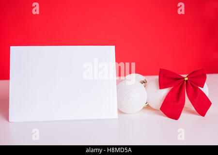 Christmas balls and red ribbon on red background - Stock Image