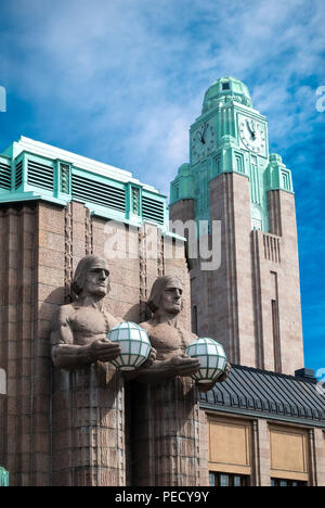 Central Railway Station Helsinki with two stone men statues holding lamps and the Station clock tower. - Stock Image