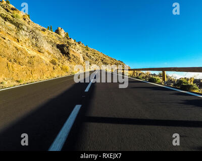Long way road at the mountain with vulcan mount in front and blue clear sky - ground point of view with black asphalt and white lines - driving and tr - Stock Image