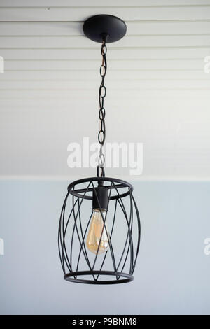 An oil-rubbed bronze pendant light, farmhouse or rustic style, hanging from a rustic beadboard ceiling. USA - Stock Image