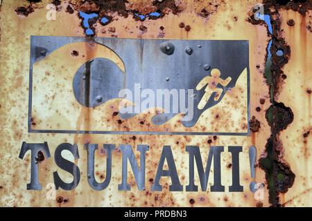 Rusty tsunami evacuation sign on beach in Sumbawa, Indonesia - Stock Image