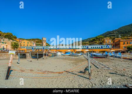 The Trenitalia train travels through the Cinque Terre village of Monterosso Al Mare with the town including church - Stock Image