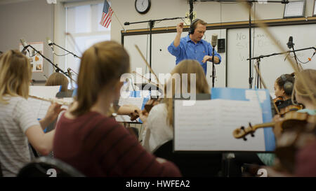 Selective focus view of teacher conducting musicians in band class - Stock Image
