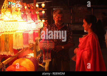 Pune, India - November 2018: An Indian shopkeeper selling his beautiful lantern to a woman shopping for Diwali festival, in India. - Stock Image
