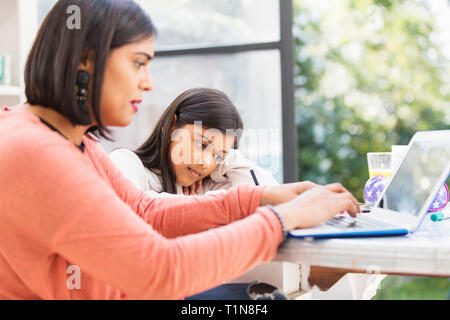 Mother and daughter using laptop, doing homework at table - Stock Image