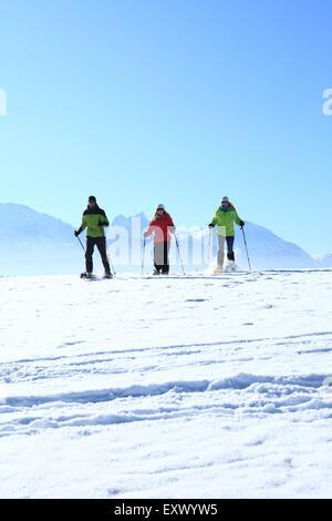 Three persons with snow shoes, Tegelberg, Ammergau Alps, Allgaeu, Bavaria, Germany, Europe - Stock Image