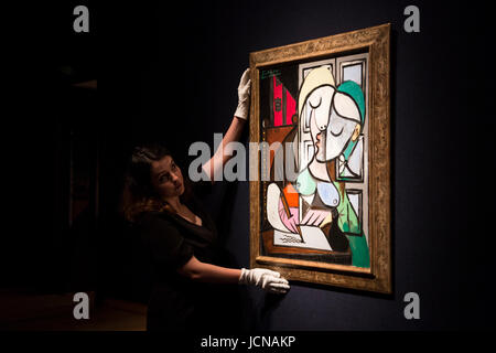 London, UK. 16 June 2017. A Christie's employee handles the painting Femem ecrivant (Marie-Therese), 1934, by - Stock Image