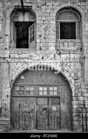 old warehouse with arched wooden door and windows, black and white - Stock Image