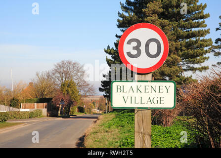 A 30 mph sign and village name on the Langham Road entering the North Norfolk village of Blakeney, Norfolk, England, United Kingdom, Europe. - Stock Image