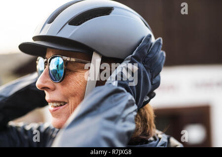 A close-up of active senior woman standing outdoors, putting on bicycle helmet. - Stock Image