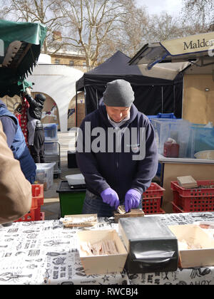 Man opening oysters in Saturday market in Chelsea - Stock Image