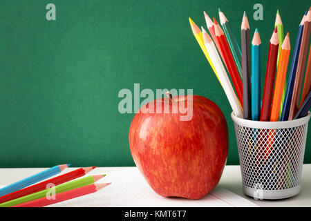Close-up of colorful pencils with big red apple near by on background of blackboard - Stock Image