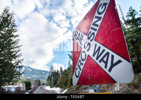 A red railway crossing sign with railroad tracks and a mountain in the background. - Stock Image