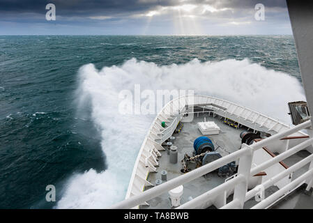 Lindblad's MS National Geographic Explorer in heavy waves in the off the coast of Svalbard with sun beams (God rays or Crepuscular rays) in distance. - Stock Image