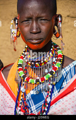 Portrait of a Maasai Woman wearing traditional clothing and jewelry in a village near the Masai Mara, Kenya, East - Stock Image