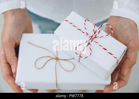 Young caucasian woman in jeans shirt holds in hands stacked gift boxes wrapped in white paper tied with striped twine. Christmas New Years corporate p - Stock Image