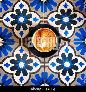 Coffee in a cafe with pretty tiled table - Stock Image