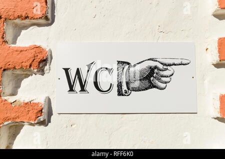 Sign pointing hand to toilets, restrooms, on vintage wall, Portugal. - Stock Image